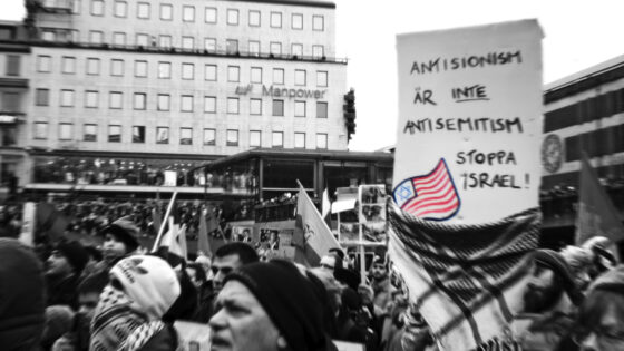 """Protesters in Stockholm, Sweden, hold a sign reading """"Anti-Zionism is not antisemitism. Stop Israel,"""" Jan. 10, 2009. (Robin/Flickr Commons)"""